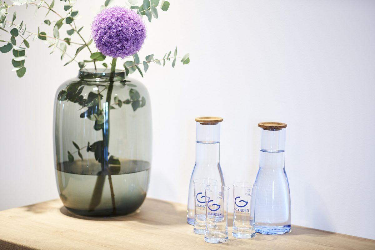 Detailaufnahme Grander Wasser mit 3 Gläsern neben Blumenvase