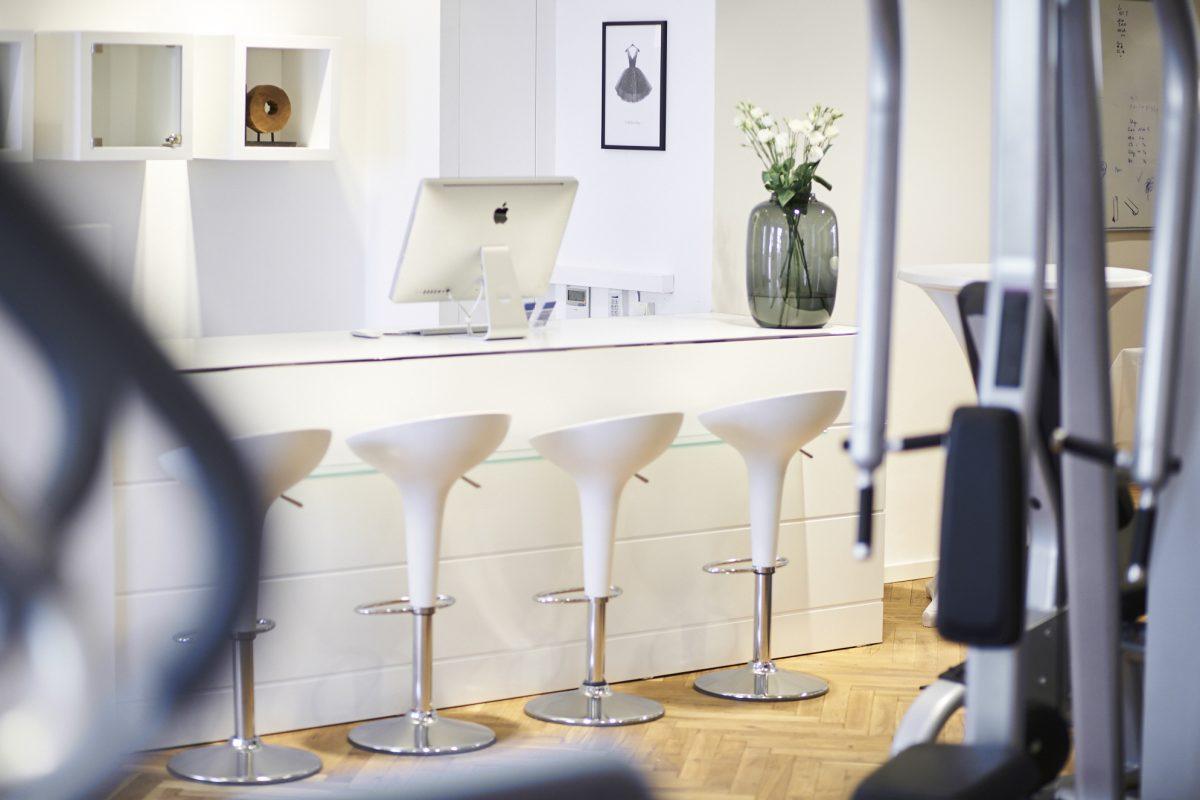 Empfangsbereich Elite Sport Club: Weißer Tresen mit weißen ovalen Barhockern, Bildschirm und Blumen auf Tresen
