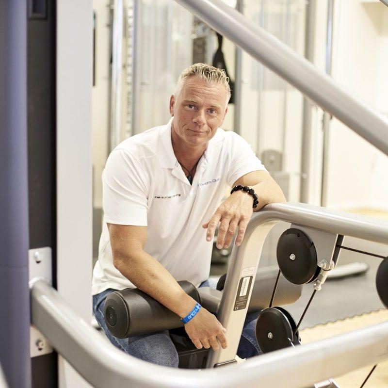 Porträt Silvio Dunkelberg, lächelnd und sitzend in Fitnessstudio an Fitnessgerät