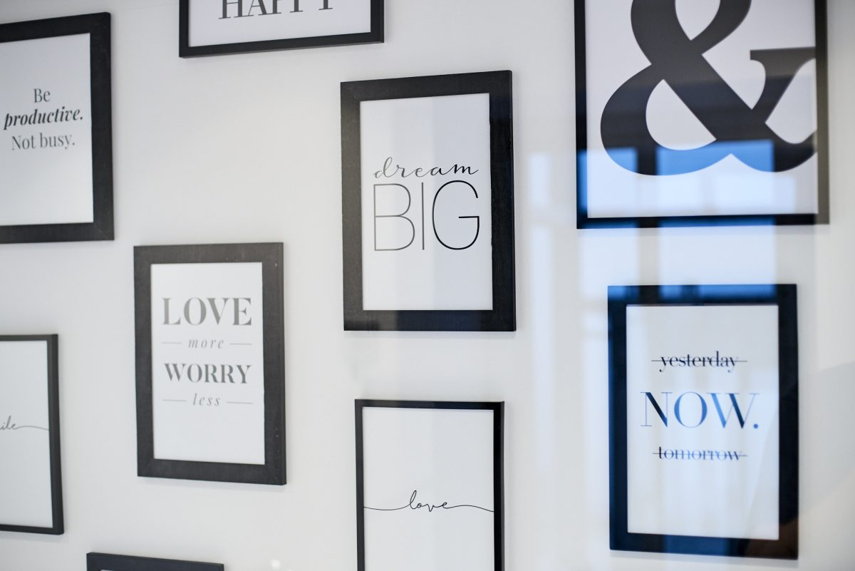 """Detailaufnahme Wand Eingangsbereich mit Bilderrahmen und Motivationssprüchen wie """"dream big"""""""