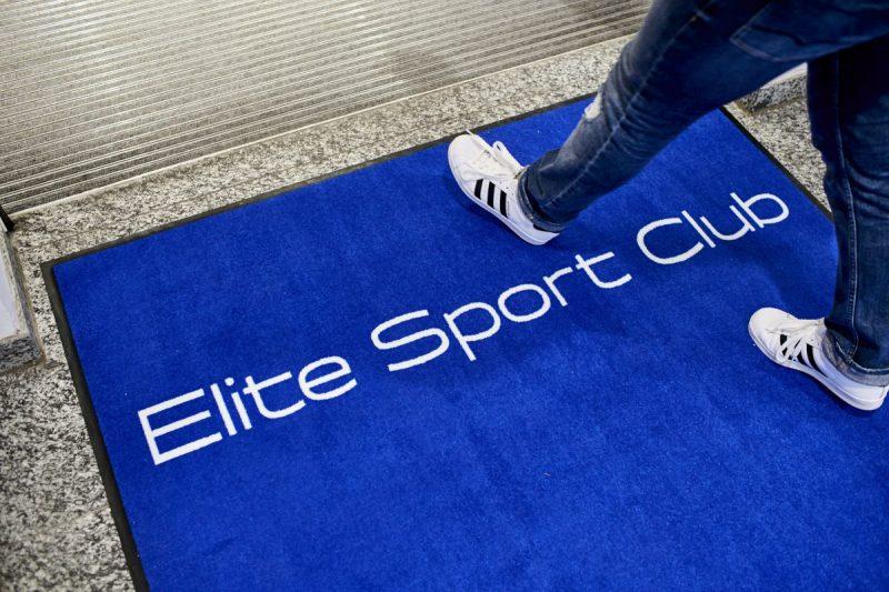 """Detailaufnahme blauer Teppich Eingang mit Schriftzug """"Elite Sport Club"""""""